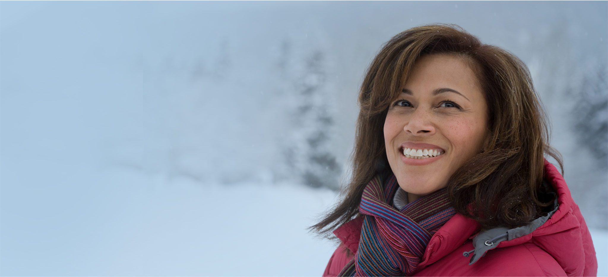 Smiling woman with a scarf in a snowstorm